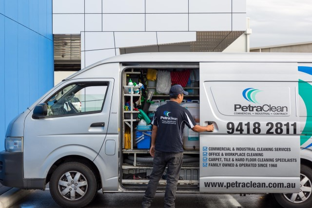PetraClean cleaner standing in front of cleaning van with door open