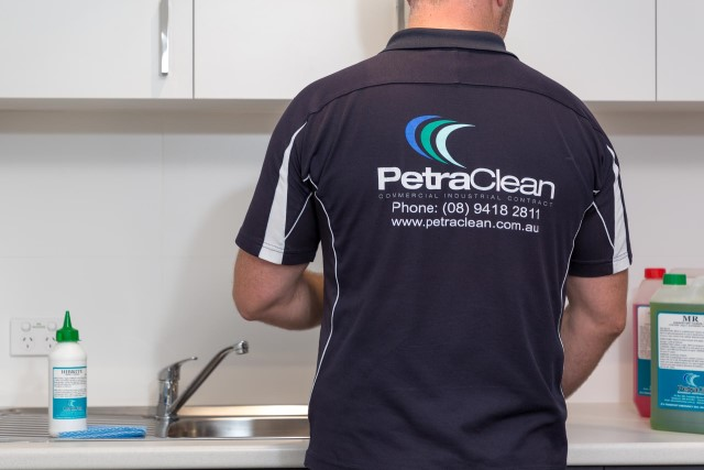 Man with PetraClean t-shirt facing away from camera at sink cleaning